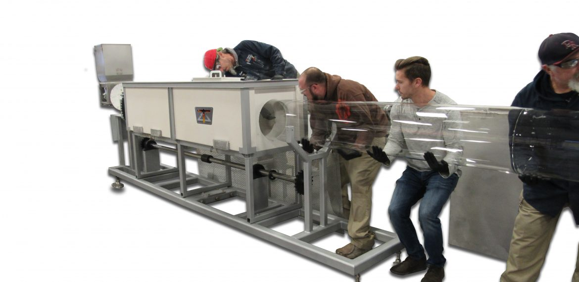 """Several men working to place a 24"""" OD quartz tube inside an opening in furnace body"""