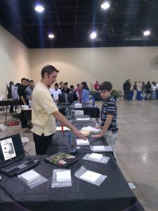 Deltech Furnaces Production Technician Bobby Duncan engages young student at AdCo Commissioners Career Expo